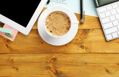 Workplace with cup of coffee, tablet and documents. Closeup stock photo