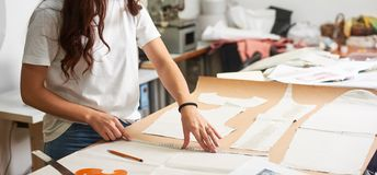 Workplace in modern design studio. Female designer creating exclusive flat paper clothing patterns. Workplace in design studio. Professional female designer royalty free stock photography