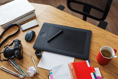 Workplace of designer illustrator. Graphic tablet surrounded by phone, camera, pencils and books Royalty Free Stock Images