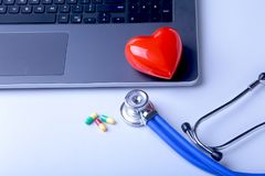 Workplace of doctor with laptop, stethoscope, red heart and assorted pils on white table. top view. Workplace of doctor with laptop, stethoscope, red heart and Royalty Free Stock Images