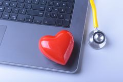 Workplace of doctor with laptop, stethoscope, red heart and notebook on white table. top view. Workplace of doctor with laptop, stethoscope, red heart and Stock Photography