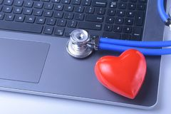 Workplace of doctor with laptop, stethoscope, red heart and notebook on white table. top view. Workplace of doctor with laptop, stethoscope, red heart and Royalty Free Stock Photo