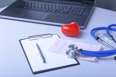 Workplace of doctor with laptop, stethoscope, red heart and RX prescription on white table. top view. Workplace of doctor with laptop, stethoscope, red heart Royalty Free Stock Photo