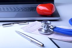 Workplace of doctor with laptop, stethoscope, red heart and RX prescription on white table. top view. Workplace of doctor with laptop, stethoscope, red heart Stock Images