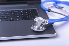 Workplace of doctor with laptop, stethoscope, RX prescription, glasses and notebook on white table. Copy space. Workplace of doctor with laptop, stethoscope, RX Stock Image
