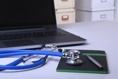 Workplace of doctor with laptop, stethoscope, RX prescription, glasses and notebook on white table. Copy space. Workplace of doctor with laptop, stethoscope, RX Stock Photography