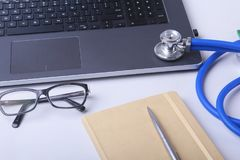 Workplace of doctor with laptop, stethoscope, RX prescription, glasses and red heart and notebook on white table. Copy. Space Stock Photography