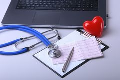 Workplace of doctor with laptop, stethoscope, RX prescription, glasses and red heart and notebook on white table. top. View. Copy space Royalty Free Stock Image