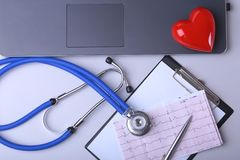 Workplace of doctor with laptop, stethoscope, RX prescription, glasses and red heart and notebook on white table. top. View. Copy space Royalty Free Stock Images