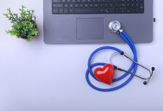 Workplace of doctor with laptop, stethoscope, RX prescription, glasses and red heart and notebook on white table. top. View. Copy space Stock Photo