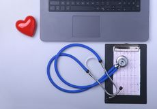 Workplace of doctor with laptop, stethoscope, RX prescription, glasses and red heart and notebook on white table. top. View. Copy space Royalty Free Stock Photo