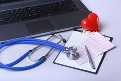 Workplace of doctor with laptop, stethoscope, RX prescription, glasses and red heart and notebook on white table. top. View. Copy space Stock Images