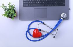 Workplace of doctor with laptop, stethoscope, RX prescription, glasses and red heart and notebook on white table. top. View. Copy space Stock Photography