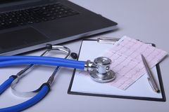 Workplace of doctor with laptop, stethoscope, RX prescription and notebook on white table. top view. Copy space. Workplace of doctor with laptop, stethoscope Stock Photo