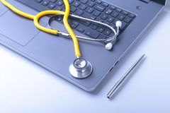 Workplace of doctor with laptop, stethoscope and RX prescription on white table. top view. Workplace of doctor with laptop, stethoscope and RX prescription on Royalty Free Stock Images