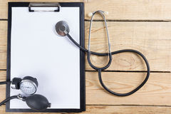 Workplace of a doctor. Medical clipboard and stethoscope on wooden desk background. Top view.  Stock Image