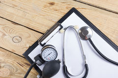 Workplace of a doctor. Medical clipboard and stethoscope on wooden desk background. Top view.  Stock Images