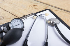Workplace of a doctor. Medical clipboard and stethoscope on wooden desk background. Top view.  Royalty Free Stock Images
