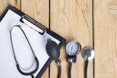 Workplace of a doctor. Medical clipboard and stethoscope on wooden desk background. Top view Stock Image