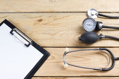 Workplace of a doctor. Medical clipboard and stethoscope on wooden desk background. Top view.  Royalty Free Stock Image
