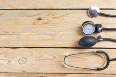 Workplace of a doctor. Medical clipboard and stethoscope on wooden desk background. Top view Royalty Free Stock Photo