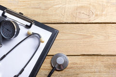 Workplace of a doctor. Medical clipboard and stethoscope on wooden desk background. Top view Royalty Free Stock Photos