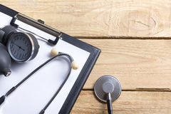 Workplace of a doctor. Medical clipboard and stethoscope on wooden desk background. Top view Royalty Free Stock Image