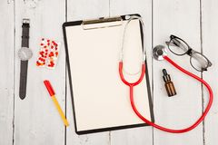 Workplace of doctor. Red stethoscope, clipboard, glasses, watch and pills on white wooden table stock images