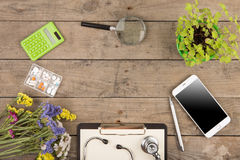 Workplace of a doctor. Stethoscope, clipboard, pills, smartphone and other stuff on wooden desk. Workplace of a doctor.Stethoscope, clipboard, pills, smartphone stock image