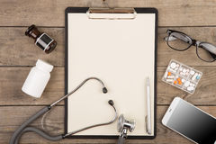 Workplace of a doctor. Stethoscope, clipboard, pills, smartphone and other stuff on wooden desk. Workplace of a doctor.Stethoscope, clipboard, pills, smartphone stock photo