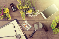 Workplace of a doctor. Stethoscope, clipboard, pills, smartphone and other stuff on wooden desk Royalty Free Stock Photo