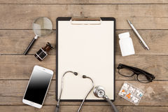 Workplace of a doctor. Stethoscope, clipboard, pills, smartphone and other stuff on wooden desk. Workplace of a doctor Stethoscope, clipboard, pills, smartphone royalty free stock photos