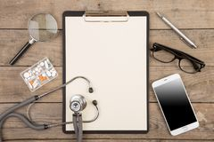 Workplace of a doctor. Stethoscope, clipboard, pills, smartphone and other stuff on wooden desk. Workplace of a doctor Stethoscope, clipboard, pills, smartphone royalty free stock images