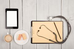 workplace of doctor - stethoscope, clipboard, tablet pc, cup of stock photos