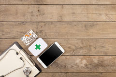 Workplace of a doctor. Stethoscope,emergency kit, and other stuff on wooden desk. Workplace of doctor. Stethoscope,emergency kit, and other stuff on wooden desk royalty free stock photo