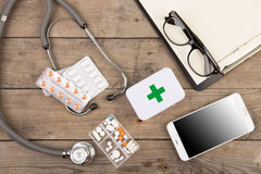 Workplace of a doctor. Stethoscope,emergency kit, and other stuff on wooden desk. Workplace of doctor. Stethoscope,emergency kit, and other stuff on wooden desk royalty free stock photography