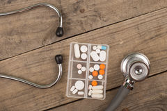 Workplace of a doctor. Stethoscope,emergency kit, and other stuff on wooden desk. Workplace of a doctor Stethoscope,emergency kit, and other stuff on wooden desk stock images