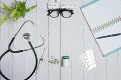 Doctor table with medical items, stethoscope and pills. Workplace of doctor - stethoscope, medical items and pills on desk stock images