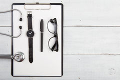 Workplace of doctor - stethoscope, medicine clipboard, glasses a Royalty Free Stock Photos