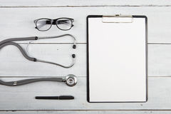 Workplace of doctor - stethoscope, medicine clipboard, glasses Stock Photos