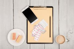 workplace of doctor - stethoscope, pills, clipboard, smartphone, cup of coffee stock photography