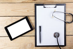 Workplace of a doctor. Tablet, stethoscope, black pen on wooden desk background. Top view. Royalty Free Stock Photography