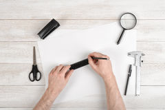 Workplace of draftsman with pencil, pen, stapler, scissors, magnifying glass. Man hands holding centimeter ruler and. Workplace of draftsman equipped with pencil royalty free stock photography