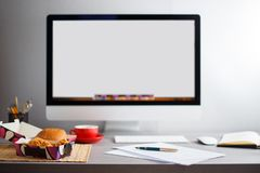 Workplace with empty monitor, lunch and papers Stock Photo