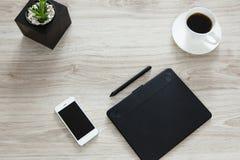 workplace En la tabla de madera hay una tableta de gráficos Imágenes de archivo libres de regalías