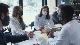 Workplace with epidemic safety measures. Young multiethnic business colleagues work at office table meeting, wear masks.