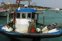 Daily workplace of a fisherman: blue and white fishing vessel on the ocean with net and fishing utilities stock images