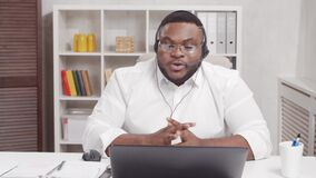 Workplace of freelancer. African-American man works at home office using computer and headset. Employee is having a