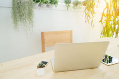 Workplace at garden, wood table with laptop, tablet, smartphone. Workplace at garden, wood table with laptop, tablet, smartphone and cactus flower on pot Stock Photo