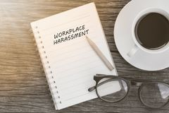 Workplace harassment concept on notebook with glasses, pencil an. D coffee cup on wooden table. Business concept royalty free stock images